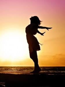 Frauen-Silouette seitlich mit ausgebreiteten Armen nach hinten vor Sonnenuntergang